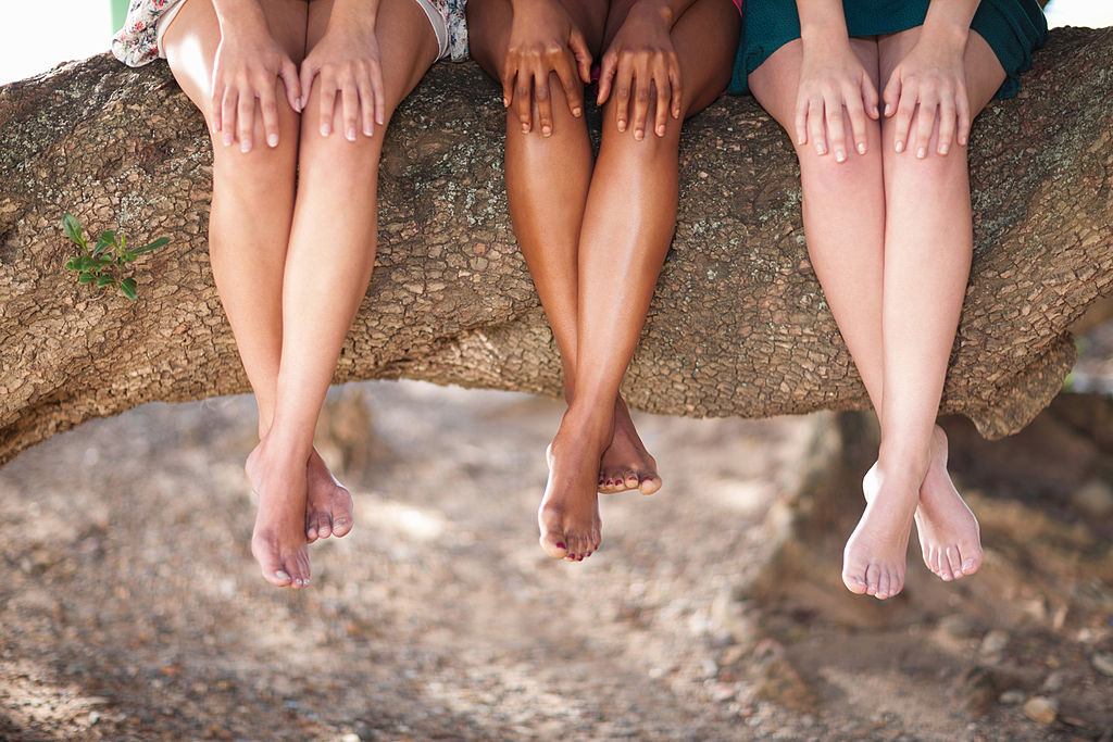 Women seated outdoors with legs on desplay