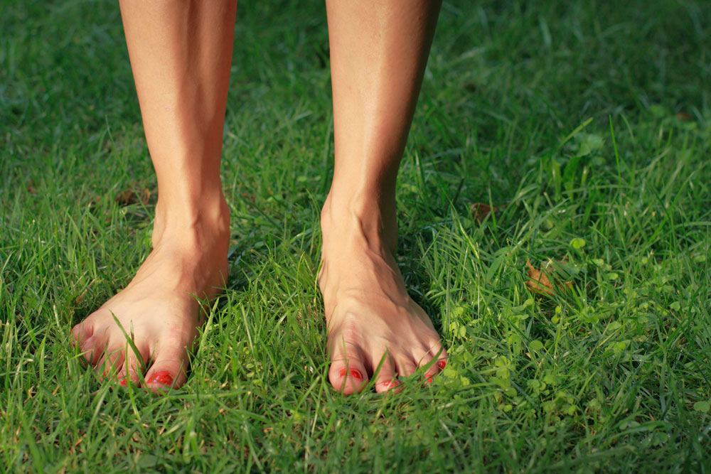 Bare legs and feet on green grass